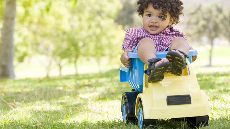 Boy playing on plastic toy dump truck